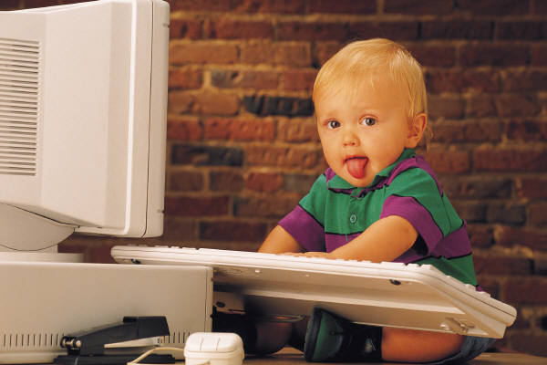 A small child sitting in front of a computer